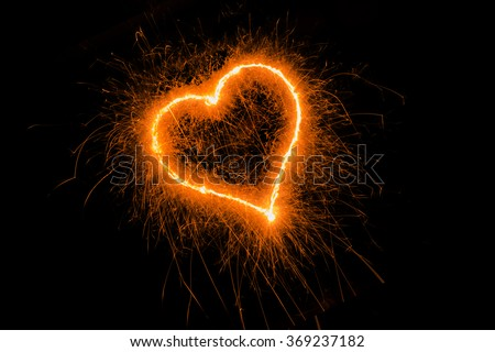 Valentines day heart gold color. Sparklers heart,  Heart of sparklers on black background,love and light. - stock photo