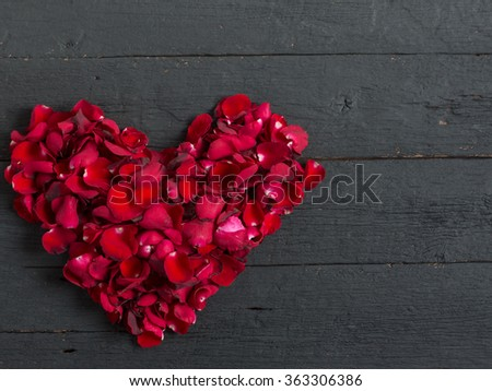 Valentines Day Heart Made of Red Roses petals on black background - stock photo