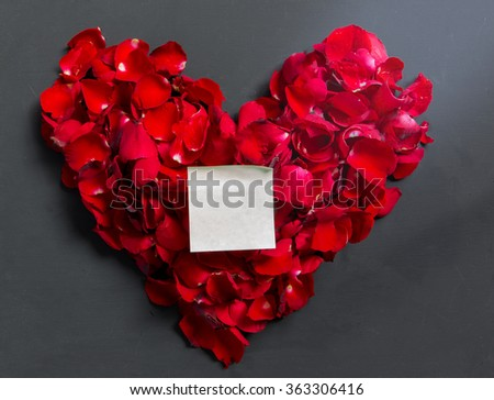 Valentines Day Heart Made of Red Roses petals with note paper on black background - stock photo