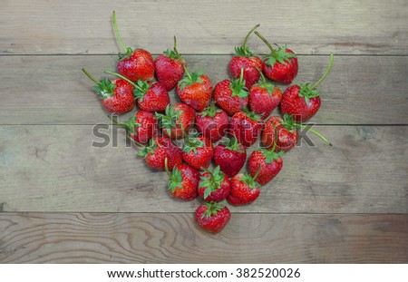Valentines Day Heart Made of strawberries on wooden board. - stock photo