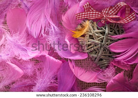 Valentines Day. Heart made of vine on beautiful pink feathers. Love concept. Retro styled, vintage - stock photo