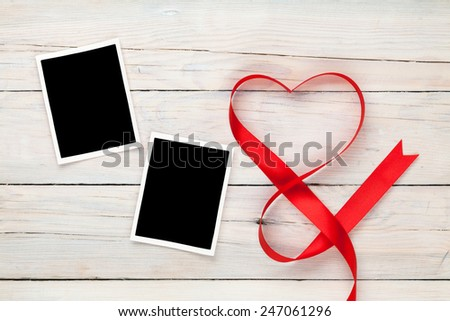 Valentines day heart shaped red ribbon and blank photo frames over wooden table background - stock photo