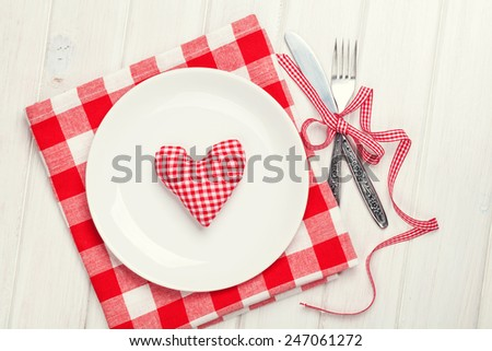 Valentines day heart shaped toy gift on plate with silverware. View from above over white wooden table - stock photo