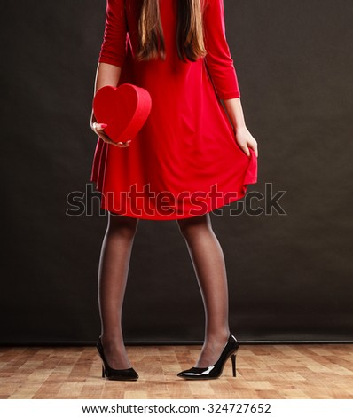 Valentines day love romance concept. Woman in red dress holding heart shaped gift box in hands dark gray background.