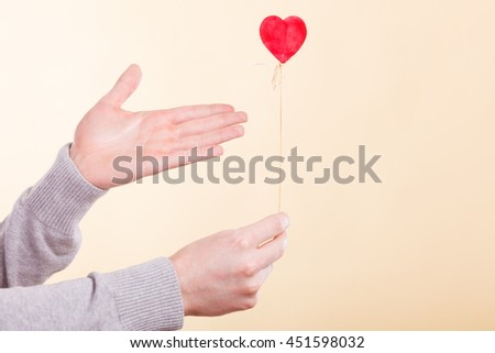 Valentines Day. Male hand holding showing red little heart on stick. Man presents palm with love sign symbol. - stock photo