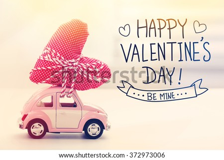 Valentines Day message with miniature pink car carrying a heart cushion - stock photo
