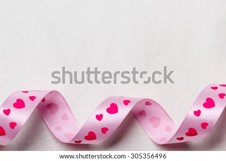 Valentines day or wedding concept. Pink heart satin ribbon on abstract white cloth background, copy space. Curves frame