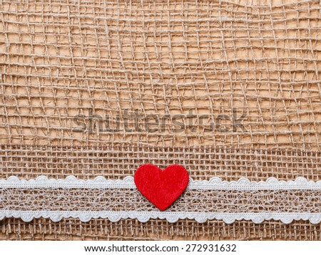 Valentines day or wedding concept. Red wooden decorative heart lace ribbon on abstract cloth burlap background with copy space - stock photo
