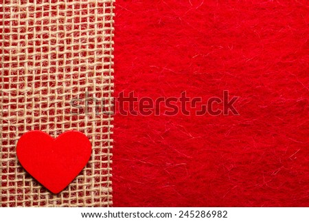 Valentines day or wedding concept. Wooden decorative heart sacking ribbon on abstract red cloth background. Border frame. - stock photo