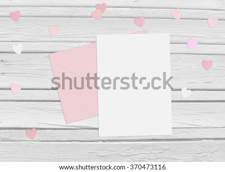 Valentines day or wedding mock up scene with envelope, blank card, paper hearts confetti and wooden background, empty space for your text, top view - stock photo