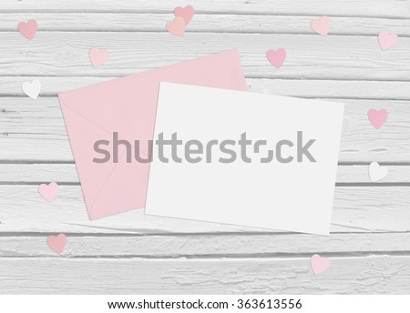 Valentines day or wedding mockup scene with envelope, blank card, paper hearts confetti and wooden background, empty space for your text, top view - stock photo