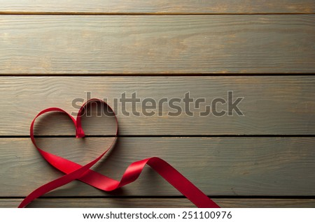 Valentines day red ribbon over a wooden background with copyspace - stock photo