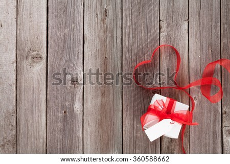 Valentines day ribbon heart and gift box on wooden table. Top view with copy space - stock photo