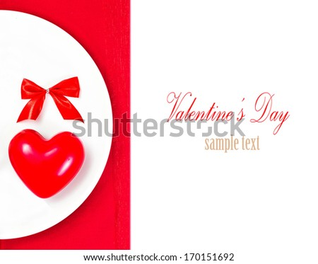 Valentines Day table setting place with copyspace. Red Heart on a white plate plate isolated on white background. Valentine Day Card