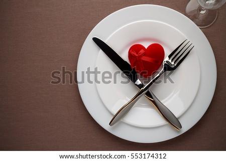 Ngày Valentine bảng thiết với trái tim màu đỏ trên một đĩa và dao kéo.  Khái niệm của bữa ăn tối lãng mạn.  Top xem, không gian sao chép.