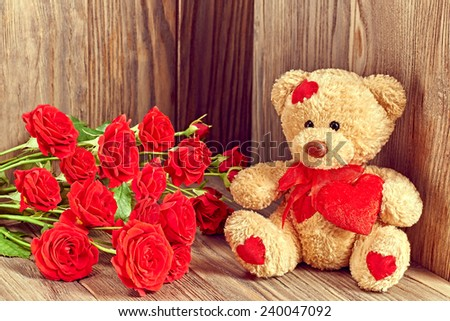 Valentines Day. Teddy Bear Loving with bouquet of Red Roses, Vintage. Retro Styled. Love concept on wooden background - stock photo