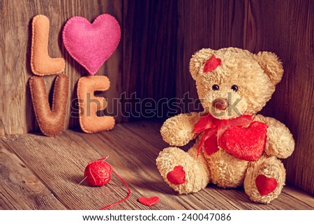 Valentines Day. Teddy Bear Loving with red hearts, Handmade word Love. Vintage. Retro Styled on wooden background - stock photo