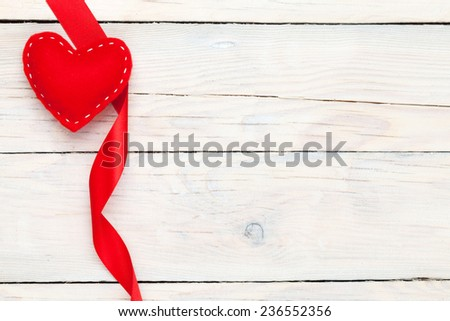 Valentines day toy heart and ribbon over wooden table background with copy space - stock photo