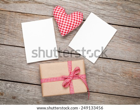 Valentines day toy heart, blank photo frames and gift box over wooden table background - stock photo