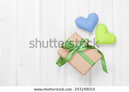 Valentines day toy hearts and gift box over wooden table background - stock photo