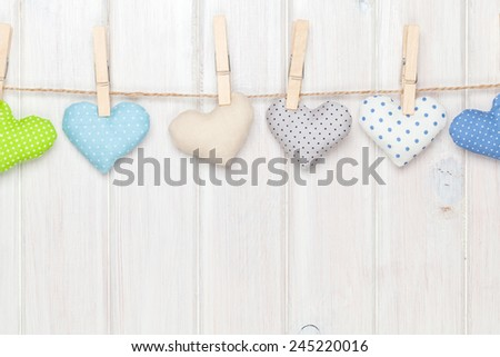 Valentines day toy hearts hanging on rope over white wooden background with copy space - stock photo