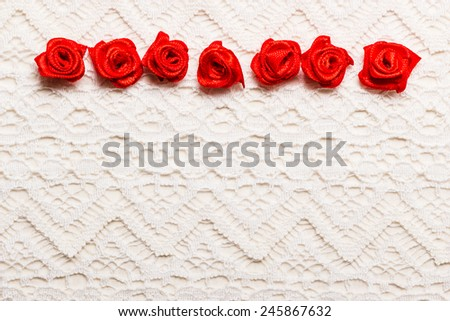Valentines day wedding, invitation or greeting card. Red decorative satin rose flowers on white cloth lace background - stock photo