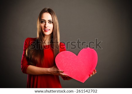 Valentines Day. Woman holding heart sign with copy space on grey background in studio. - stock photo