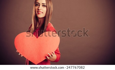 Valentines Day. Woman holding heart sign with copy space studio shot. Vintage retro photo. - stock photo