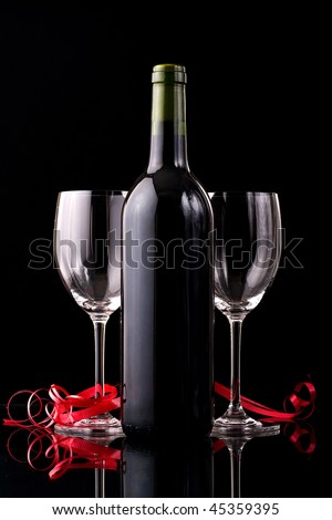 Valentines Dinner setup with two glass and a bottle of red wine - stock photo