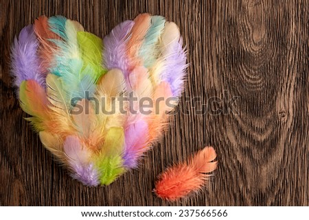 Valentines Heart Shape made of colorful feathers. Love concept on wooden background. Retro - stock photo