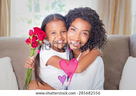 Valentines love hearts against pretty mother sitting on the couch with her daughter holding roses - stock photo