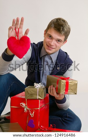 Valentines Man /  Teenager holding heart and gifts isolated on white background - stock photo