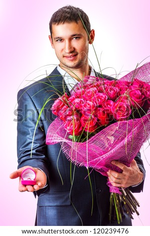 Valentines Man with flowers and ring un pink box. Proposal scene - stock photo