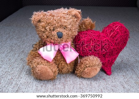 Valentines Teddy Bear with red hearts sitting alone - stock photo