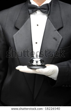 Valet or butler holding service bell in gloved hand in front of body, torso only - stock photo