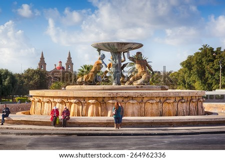 VALETTA, MALTA - JANUARY 18 2015: Famous Valetta landmark Triton fountain with locals and tourists nearby - stock photo