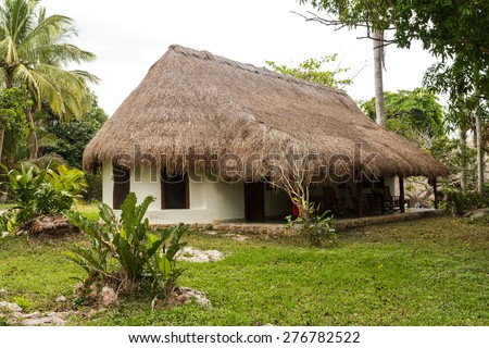 VALLADOLID, MEXICO - March 27, 2015: Obvious signs of wear are visible on this block and stucco home with rusty worn corrugated metal roof in Valladolid, Yucatan - stock photo