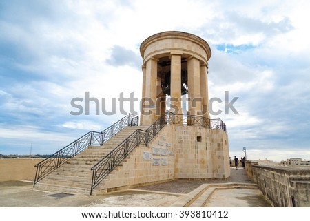 VALLETTA, MALTA - OCTOBER 30, 2015 : View of the bell tower of Siege Bell Memorial in Valletta, Malta, on cloudy blue sky background. - stock photo