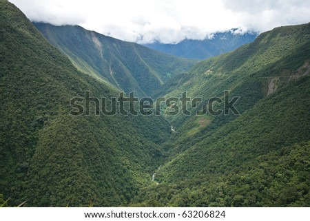 Valley covered in rainforest in the Yungas region of Bolivia, on the eastern slopes of the Andes, leading into Amazon rainforest - stock photo