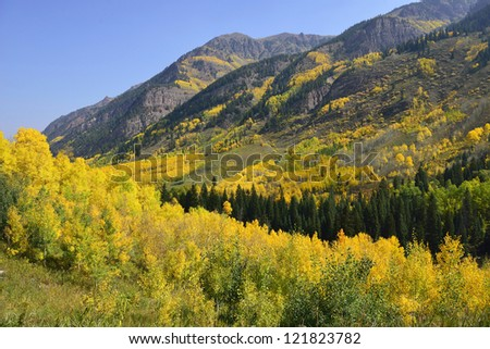 valley in the mountains of Colorado with golden and green aspen during foliage season - stock photo