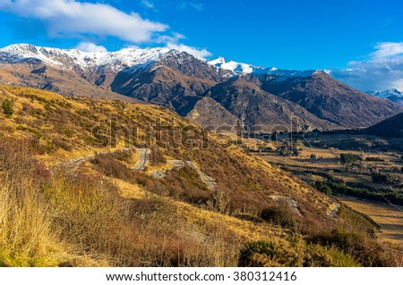 Valley view from Crown Range road, New Zealand. Scenic valley view from Crown Range road, Queenstown, New Zealand. Winding mountain road. Beautiful mountain landscape - stock photo