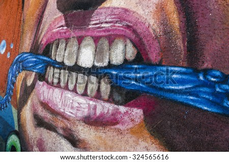 VALPARAISO, CHILE - OCTOBER 29, 2014: Colourful graffiti detail of an aggressive face with scarf between the teeth in Valparaiso, Chile. Valparaiso Historic center is a UNESCO world heritage site - stock photo