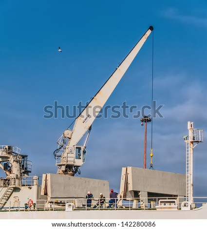 VALPARAISO, FEBRUARY 6: Cargo ship crane with workers at harbour on February 6, 2011 in Valparaiso, Chile. Valparaiso is the main industrial port of Chile. - stock photo
