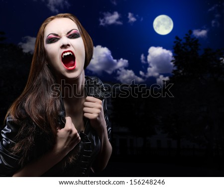 Vampire girl on night sky background - stock photo