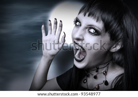 Vampire gothic style for halloween. Portrait of screaming young brunette woman with fangs - stock photo