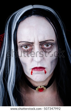 Vampire Halloween Woman portrait. Vampire Girl with dripping blood from her red lips. Vampire makeup and costume for Halloween party.