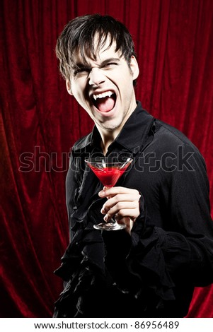 Vampire is holding a bloody halloween drink and showing his fangs - stock photo