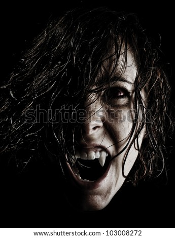 Vampire with long wet curly hair, fangs and red eyes ready to feed in the night - stock photo