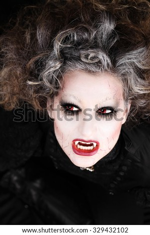 vampire woman portrait with mouth open showing teeth canines, halloween make up