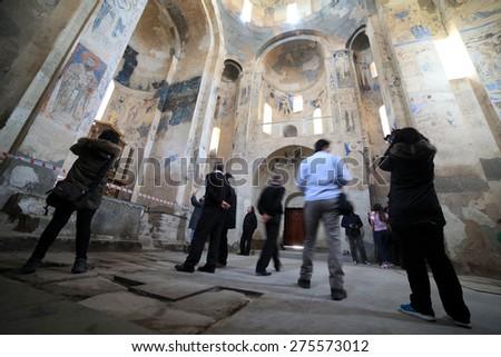 VAN,TURKEY-APRIL 28: Unidentified tourists visiting the Akdamar Church.Armenian Church of the Holy Cross stands on Akhtamar Island (Akdamar) in Lake Van on April 28,2015 in Van,Turkey. - stock photo